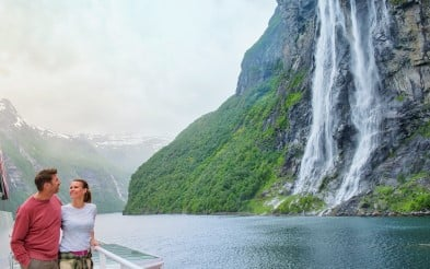 Couple admiring the Seven Sisters waterfall on Hurtigruten ship in Geirangerfjord