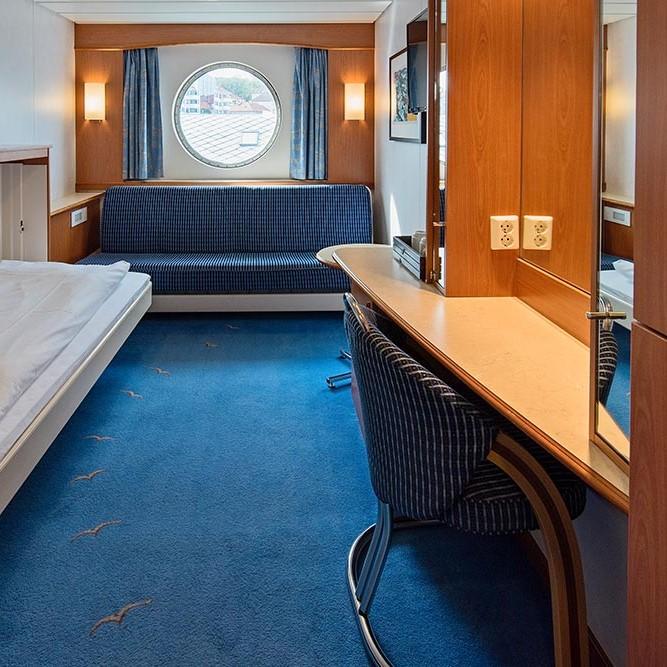 Et soverom med en seng og skrivebord i et lite rom