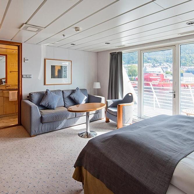 Et hotellrom med en seng og et stort vindu