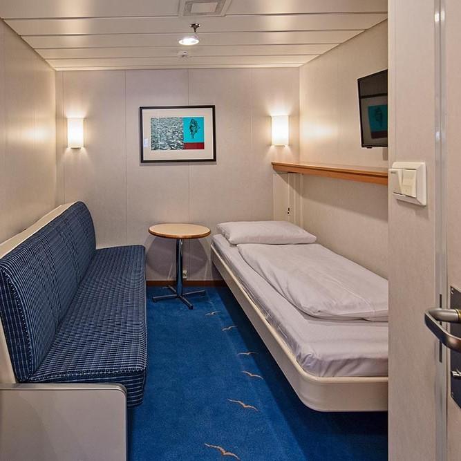 Et soverom med en seng og en stol i et rom