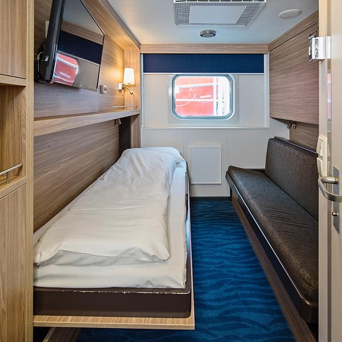 Et soverom med en seng og skrivebord i et rom